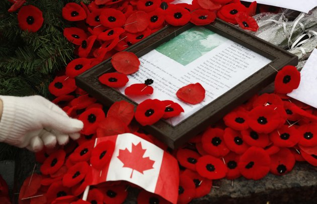 Reuters/REUTERS - A woman places a poppy on the Tomb of the Unknown Soldier following the Remembrance Day ceremony at the National War Memorial in Ottawa November 11, 2013. REUTERS/Chris Wattie